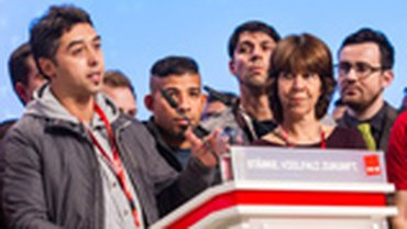 Zwei von 2000 Flüchtlingen berichteten den Delegierten darüber, wie sie in der Nachbarhalle leben.