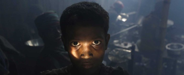 A Bangladeshi child worker poses during a break as he makes aluminium bowls at a small factory in Dhaka, Bangladesh, 25 August 2014. The workers get 2/3 euro per day while they work in unsafe conditions.