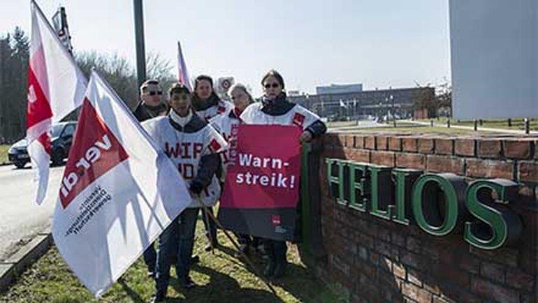 Fünf Mitarbeiter des Helios-Klinikums Berlin-Buch stehen am 19. März 2015 in Berlin mit Fahnen und Transparenten vor dem Klinikum-Areal