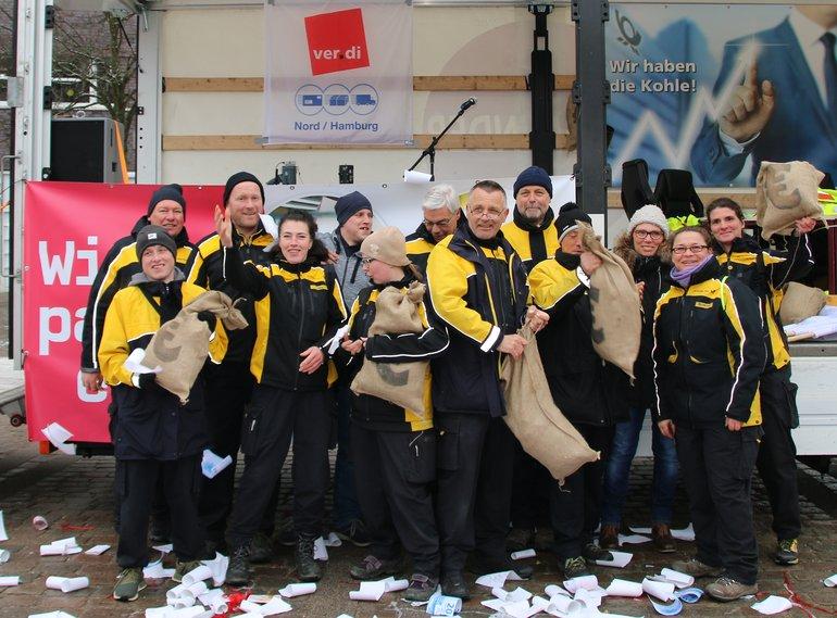 """Hamburg: Gemäß dem Motto: Wir packen es an, zogen Streikende der Post AG das rollende Vorstandsbüro in Form eines Lastwagens über den Marktplatz und holten sich symbolisch die Kohle, die ihnen zusteht. """"Die Deutsche Post AG, ein gesundes Unternehmen, das Milliardengewinne erwirtschaftet, ist in der Verantwortung, ein einigungsfähiges Angebot vorzulegen, statt sich über den berechtigten Protest der Beschäftigten zu wundern"""", sagte der Landesbezirksfachbereichsleiter für Postdienste Lars-Uwe Rieck."""