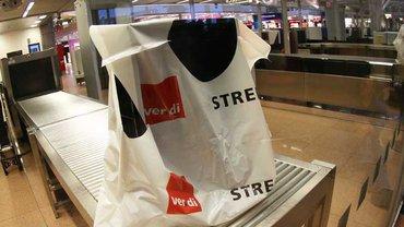 Eine Streikweste von ver.di hängt an einem Kontrollband vor der Sicherheitskontrolle im Flughafen in Hamburg