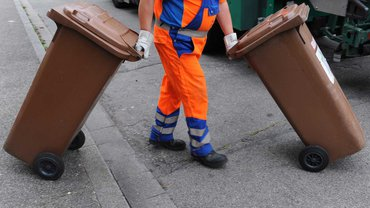 Ein Mitarbeiter der Abfallwirtschaft und Stadtreinigung schiebt eine braune Tonne mit Biomülltonne