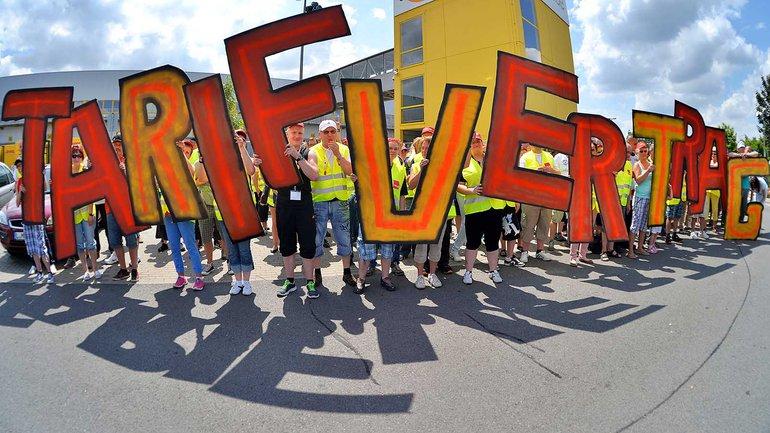 """Beschäftigte des Internet-Versandhändlers Amazon bilden während ihres Streiks das Wort """"Tarifvertrag"""" aus Pappbuchstaben."""