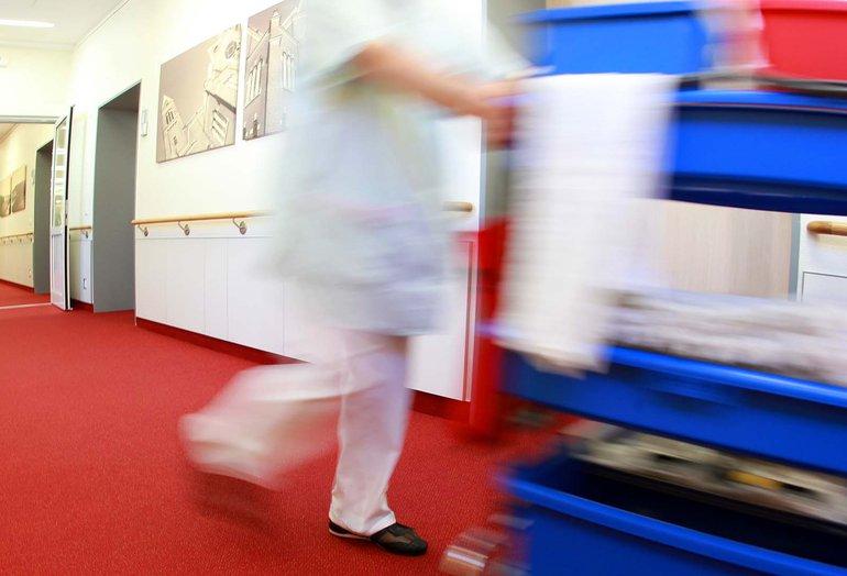 Reinigungskraft schiebt Putzwagen durch ein Krankenhaus