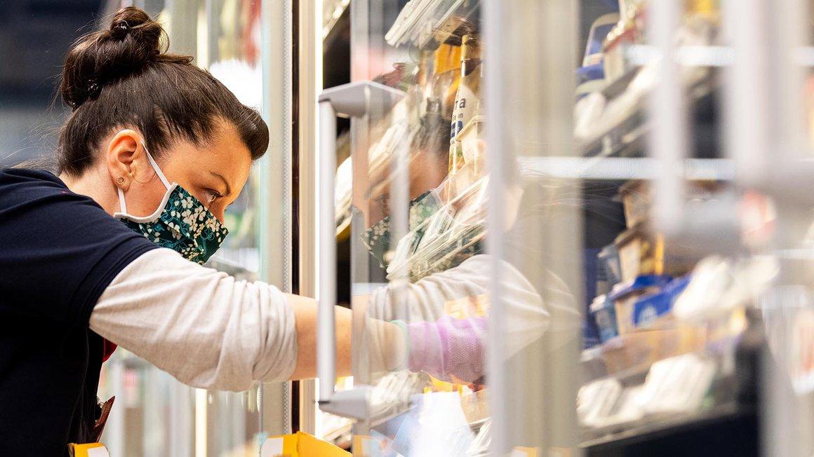 Eine Mitarbeiterin in einem Supermarkt bestückt mit Mundschutz vor Ladenöffnung ein Regal
