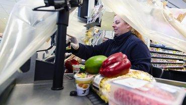 Eine Kassiererin scannt Waren in einem Edeka-Supermarkt im Kreis Schleswig-Flensburg unter einer Plastikfolie. Mit der Schutzmaßnahme wollen sich die Mitarbeiter vor einer möglichen Ansteckung durch die Kunden schützen