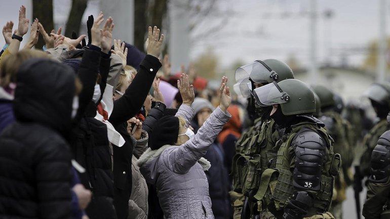 Demonstranten stehen mit erhobenen Händen während einer Kundgebung der belarussischen Opposition vor einer Reihe von Polizisten. Trotz neuer Gewaltandrohung demonstrieren immer wieder zehntausende Menschen gegen Präsident Lukaschenko