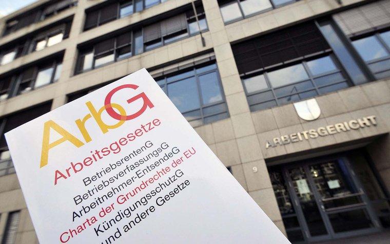 Ein Buch mit Arbeitsgesetzen wird in Köln vor das Gebäudes des Arbeitsgerichtes gehalten. Wurde das Kündigungsschutzgesetz nicht eingehalten, geht es im Streitfall vors Arbeitsgericht